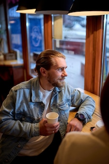 Handsome bearded guy drinking coffee in cafe, smiling, looking at side