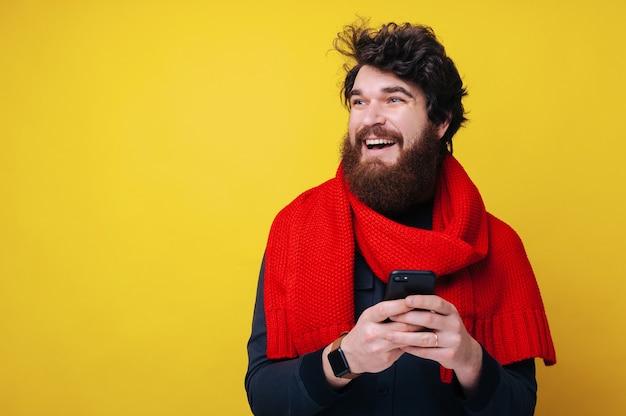 赤いスカーフでハンサムなひげを生やした男、彼の携帯電話でsmsを入力し、目をそらして考え、黄色の背景の上に