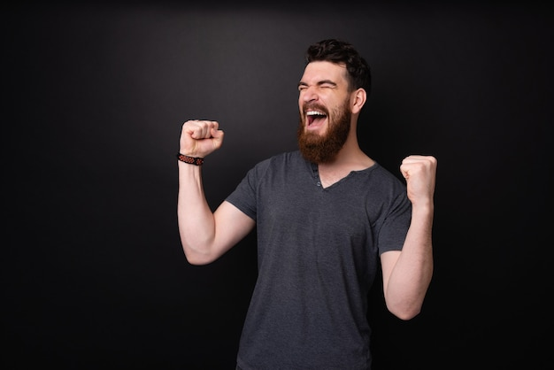 ハンサムなひげを生やした男が勝者であり、暗い背景の上にバラの手で叫んで祝っています