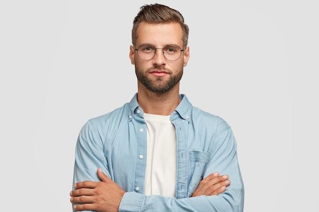 Bel ragazzo barbuto in posa contro il muro bianco