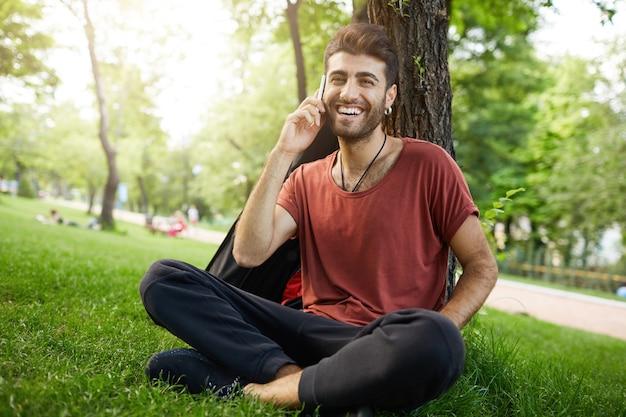 ハンサムなひげを生やした男が公園の芝生の上で休んで、携帯電話で話し、幸せな笑顔