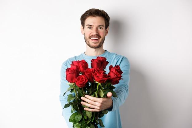 Bel ragazzo barbuto allunga le mani, regala un mazzo di rose e sorride, porta fiori in un appuntamento romantico, festeggia il giorno di san valentino con l'amante, in piedi su sfondo bianco