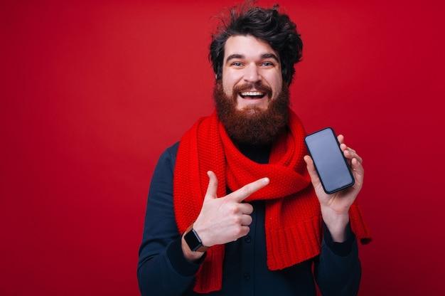 孤立した背景の上に、赤いスカーフを身に着けて、カメラを見ながらモバイル画面を指しているハンサムなひげを生やした男