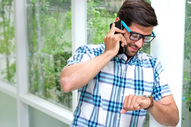 Handsome bearded guy wearing glasses is looking the watch while talking on cellphone when approaching work time.