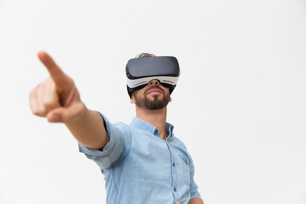 Handsome bearded guy wearing vr glasses, touching air