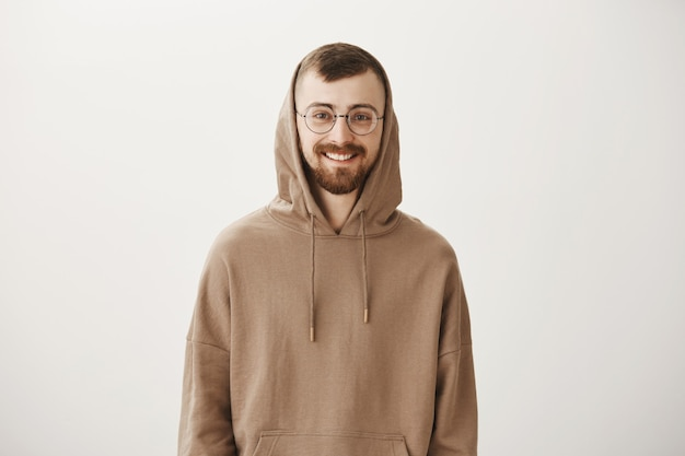 Handsome bearded hipster guy in hoodie and glasses smiling