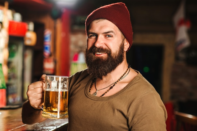 Handsome bearded hipster holds glass of beer