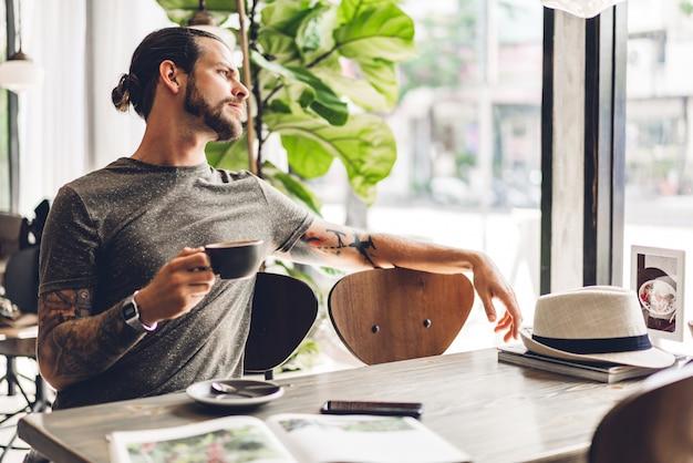 ハンサムなひげを生やした流行に敏感な男がカフェのテーブルに座ってコーヒーを飲みながらリラックス