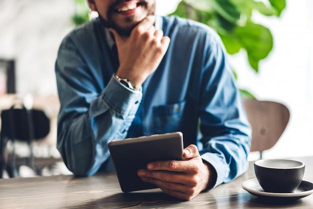 ハンサムなひげを生やした流行に敏感な男が椅子に座ってタブレットコンピューターを使用してリラックス。技術とコミュニケーションの概念 Premium写真