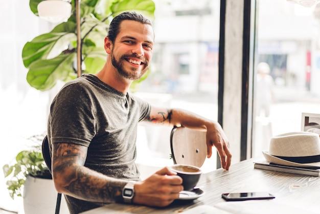 カフェのテーブルに座ってリラックスしたハンサムなひげを生やした流行に敏感な男