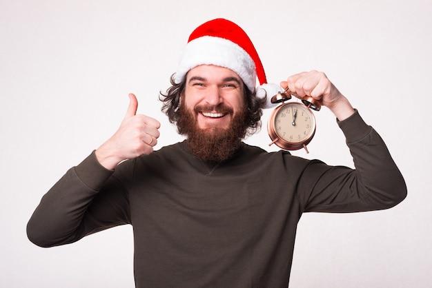 親指を立てて目覚まし時計を保持しているハンサムなひげを生やしたヒップスターの男