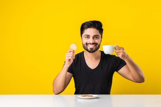 Красивый бородатый индийский мужчина ест здоровое цельнозерновое печенье, смоченное в кофе или чае в чашке, сидя за столом на желтом фоне