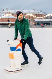 Handsome bearded male being on ice rink, learns to skate with aid or prepares for skating competitions