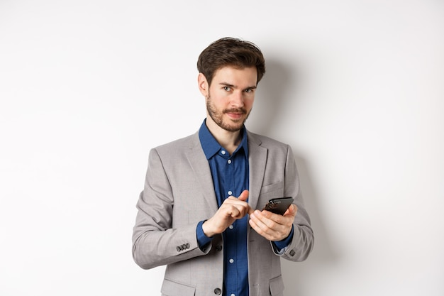 Handsome bearded male model in suit using mobile phone, smiling pleased at camera, white background.