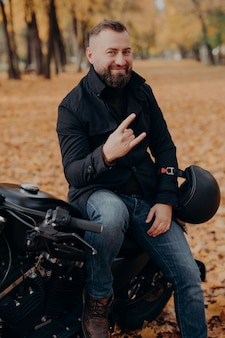 Handsome bearded male motorcyclist makes horn gesture with fingers, feels cool, wears black coat and jeans, sits on fast motorbike