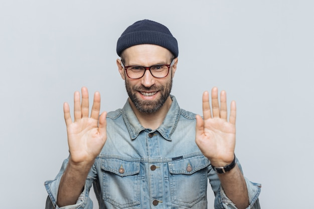 Handsome bearded male shows palms, demonstrates refusal sign