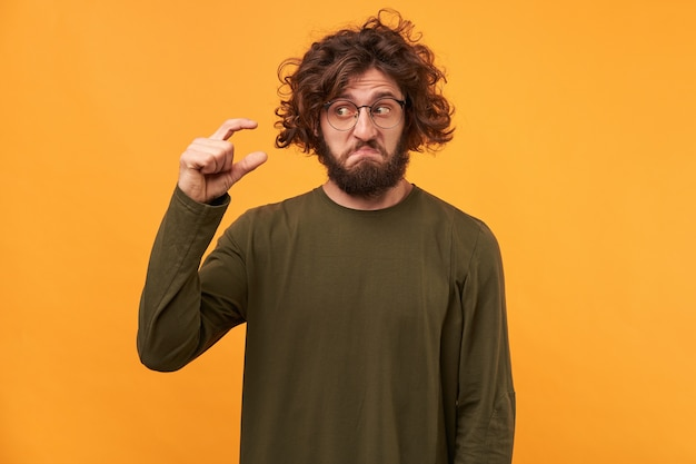 Handsome bearded male with dark curly hair, shows something tiny with hands