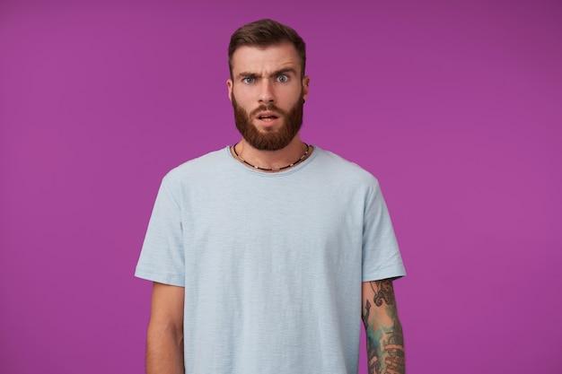 놀란 얼굴로 문신을 한 잘 생긴 수염 난 남성, 파란색 티셔츠와 트렌디 한 액세서리를 착용하고 얼굴을 찌푸리고 보라색에 서있는 동안 눈썹을 올리십시오.