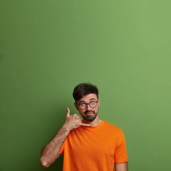 잘 생긴 수염 난 남자가 나에게 전화를 걸고, 제스처 전화 기호를 요구하고, 위쪽으로 보이며, 누군가와 계속 연락하고, 밝은 옷을 입고, 녹색 벽에 고립되어, 위의 광고 공간을 복사합니다.