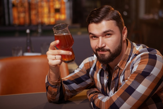 Handsome bearded man cheering to the camera with his beer glass