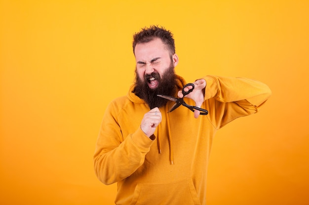 Bell'uomo barbuto che chiude gli occhi mentre usa le forbici per tagliarsi la barba su sfondo giallo. espressione facciale