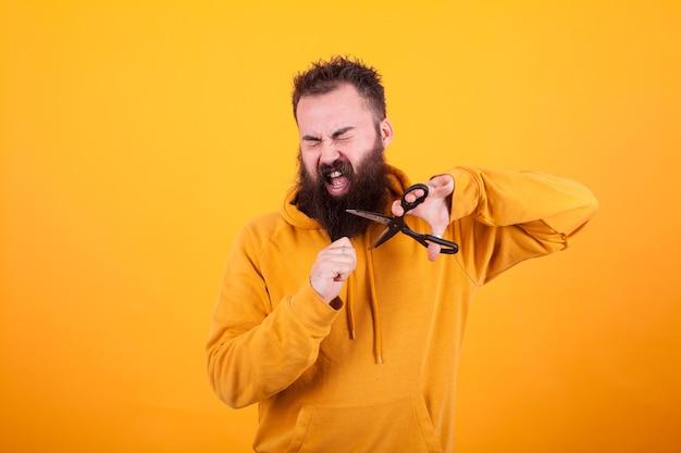 수염을 기른 잘생긴 남자가 가위를 사용하여 노란색 배경 위에 수염을 자르면서 눈을 감고 있습니다. 표정