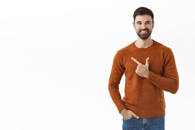 Handsome bearded man, company owner inviting support his start-up, pointing finger left, showing info smiling pleased, recommend click and find out