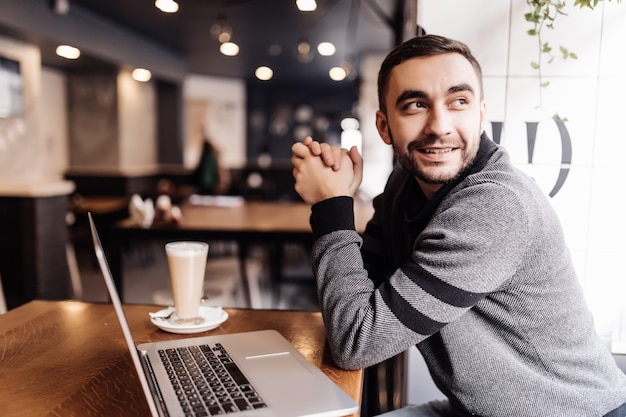 Handsome bearded man drinking coffee while working in a cafe