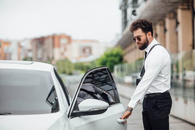 Handsome bearded man entering his car while standing outdoors on the streets of the city near the modern office center