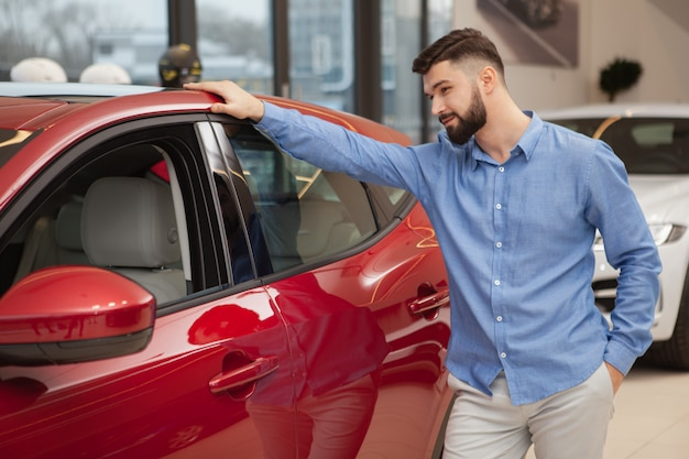 Handsome bearded man examining red automobile at car dealership.