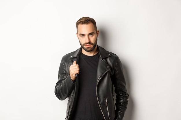 Красивый бородатый мужчина выражает уверенность, трогает свою кожаную куртку и выглядит самоуверенно