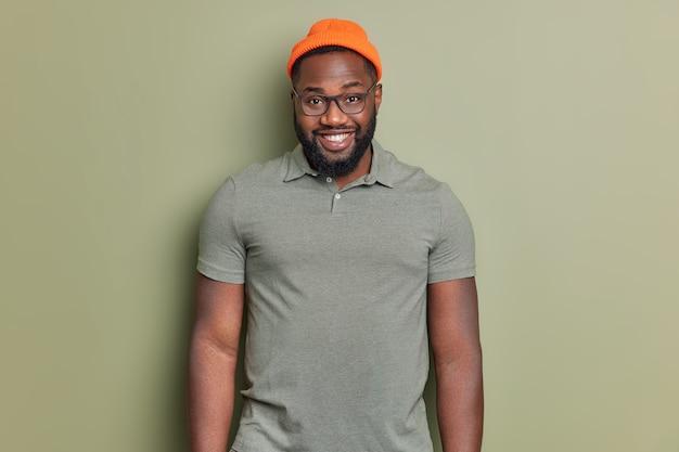 잘 생긴 수염 난 남자는 카키색 벽 위에 절연 주황색 모자와 티셔츠를 입고 행복하다고 느낍니다.