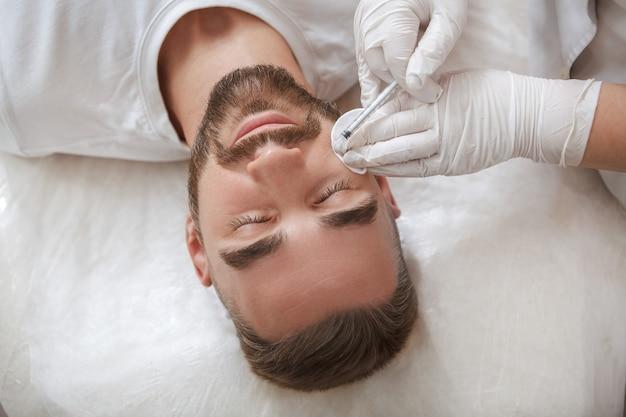 美容師による顔の注射を受けるハンサムなひげを生やした男