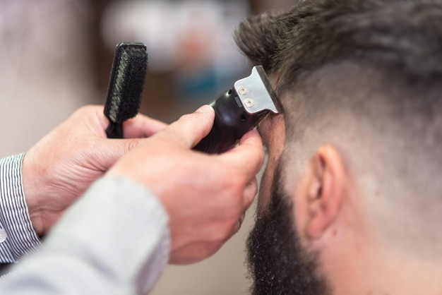 Handsome bearded man, getting haircut by barber
