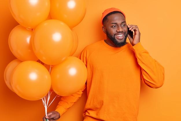 ハンサムなひげを生やした男はスマートフォンを介して幸せな話をしています前向きなイベントを祝うパーティーで友人を招待しますオレンジ色の壁に分離された風船で部屋を飾ります