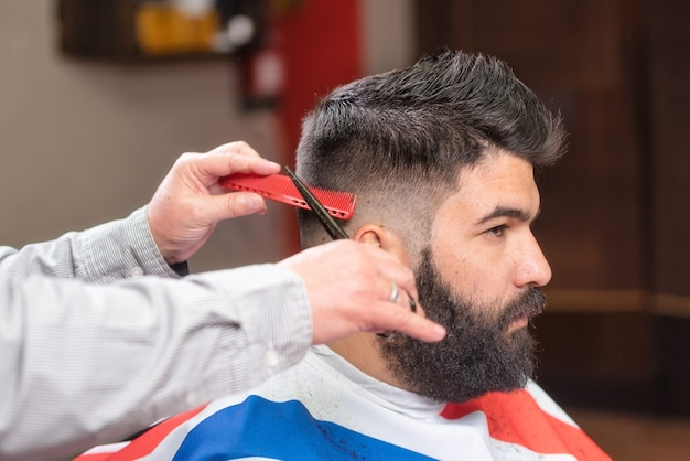 Handsome bearded man, having hair cut by scissors at barber shop.