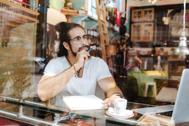 Красивый бородатый мужчина держит ручку, готовый написать
