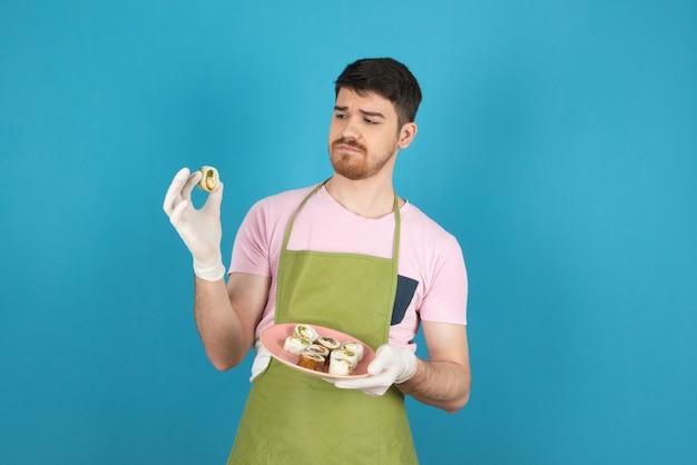 Bell'uomo barbuto che tiene i rotoli di torte fatte in casa e lo guarda.