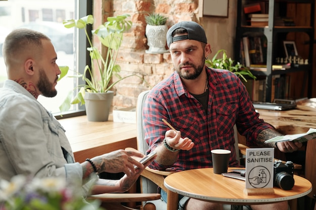 Красивый бородатый мужчина в бейсболке и повседневной рубашке сидит за столом в современном кафе и пьет кофе с другом, обсуждая работу