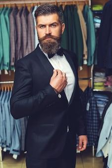 黒のタキシードでハンサムなひげを生やした男。仕立て、仕立て。メンズスーツ、彼のワークショップで仕立てます。エレガントな男のスーツが一列にぶら下がっています。エレガントなメンズブティックのラックにある高級メンズクラシックスーツ。