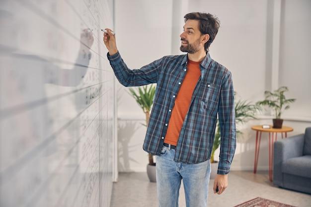 プロジェクト戦略と笑顔に取り組んでいる市松模様のシャツのハンサムなひげを生やした男