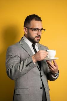 Красивый бородатый мужчина в очках в формальной одежде держит чашку кофе, изолированную на желтом