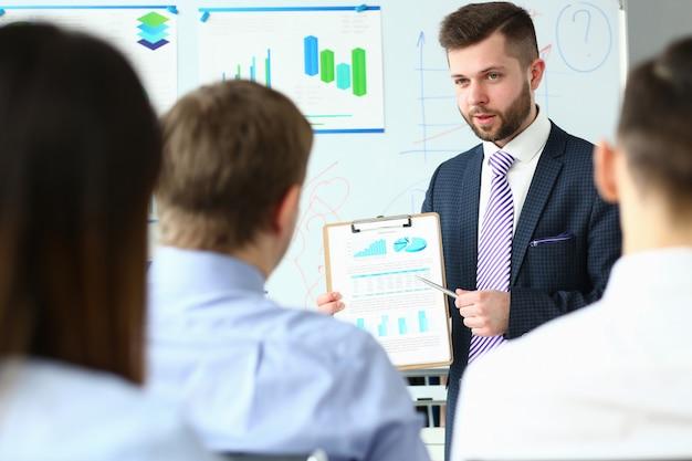 Красивый бородатый человек в костюме и галстуке, показывая студентам документ, закрепленный на блокноте