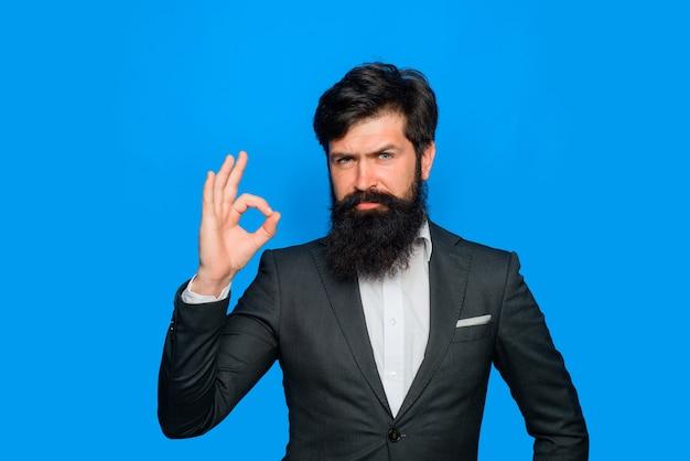 スーツのハンサムなひげを生やした男は大丈夫シンボルビジネス成功の概念をやって大丈夫サインクールな男を示しています