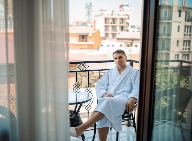 朝はローブのホテルの部屋に座っているハンサムなひげを生やした男。若い男がシャワー浴後白いバスローブを着ています。 gygieneコンセプト