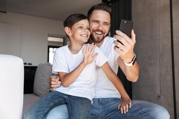 Красивый бородатый мужчина в помещении дома с сыном ребенком