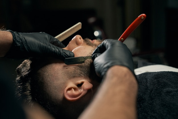 Handsome bearded man is getting shaved by hairdresser