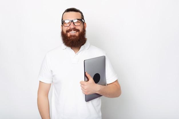 수염을 기른 잘생긴 남자가 흰색 배경 위에 닫힌 노트북을 들고 있습니다.