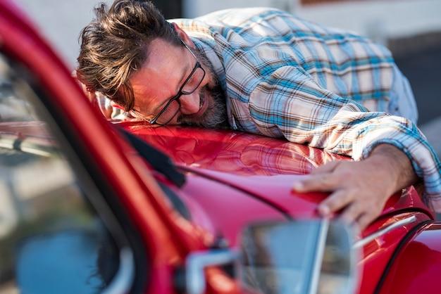 ハンサムなひげを生やした男は彼の新しい車を抱き締めて笑っています-愛と幸せの大人の成熟した人々との自動車への愛-男性と自動車の概念