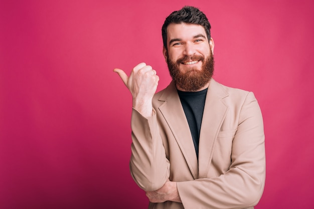 Handsome bearded man is poiting with his thumb smiling at the camera.